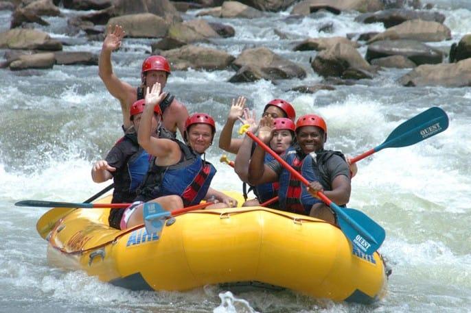 people waving while rafting